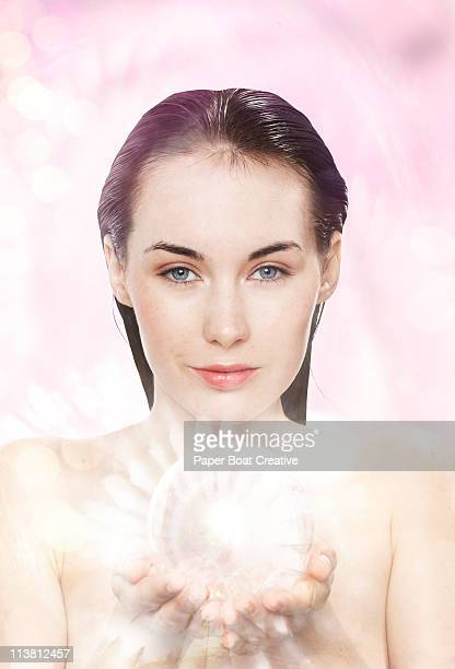 Young woman holding a glowing glass ball