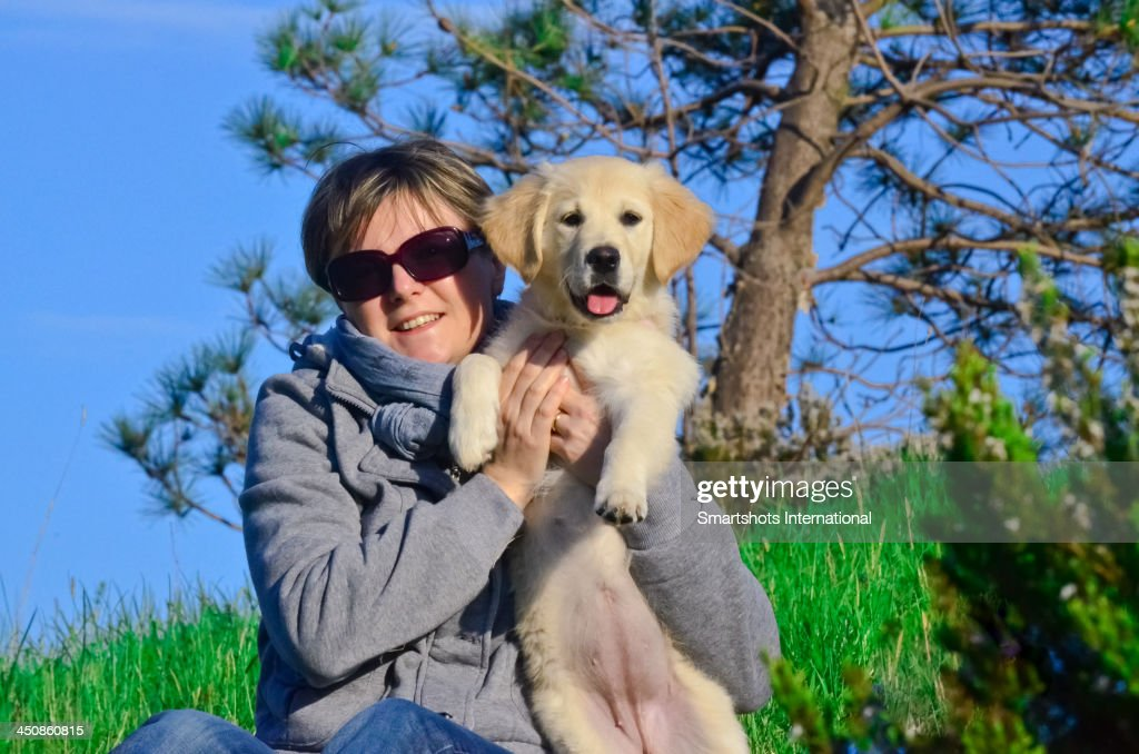Young woman holding a Golden Retriever puppy : Stock Photo