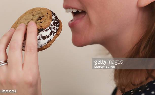 Young woman holding a gourmet ice cream sandwich made at home Vanilla ice cream in between two chocolate chip cookies