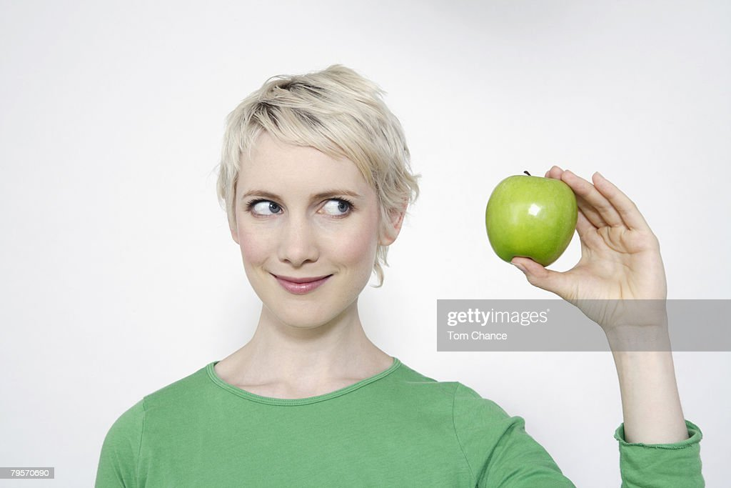 Young woman holding a green apple, portrait : Stock Photo