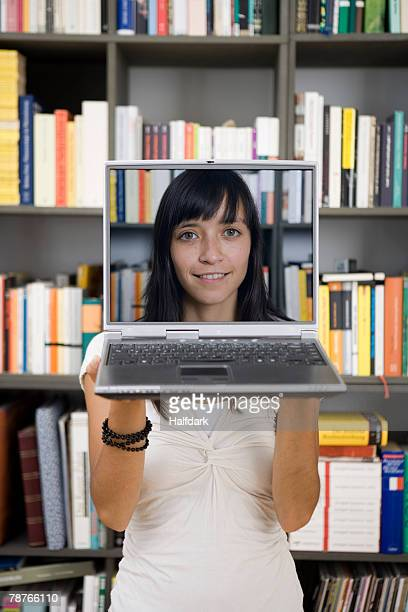 A young woman holding a laptop in front of her face