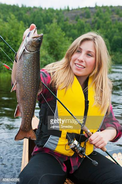young woman holding a large brook trout; ontario, canada - speckled trout stock photos and pictures