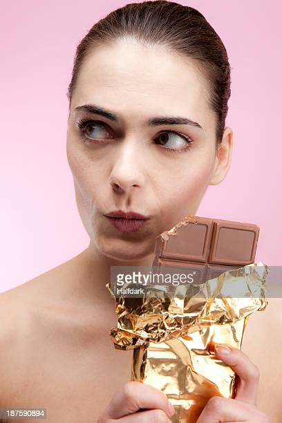 A young woman holding a large chocolate bar looking guilty