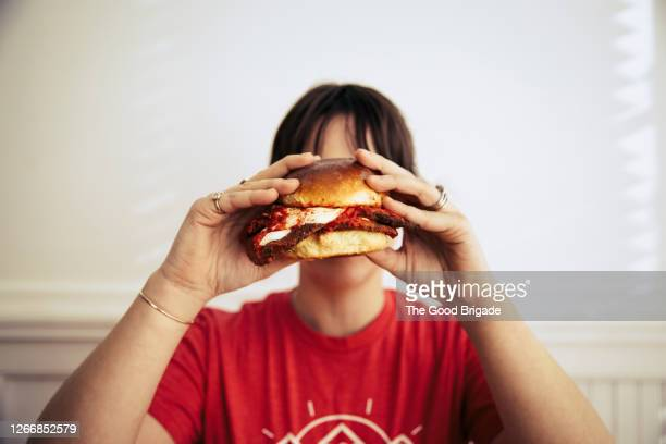 young woman holding a large sandwich - offbeat stock pictures, royalty-free photos & images