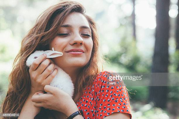 young woman holding a little white bunny at nature