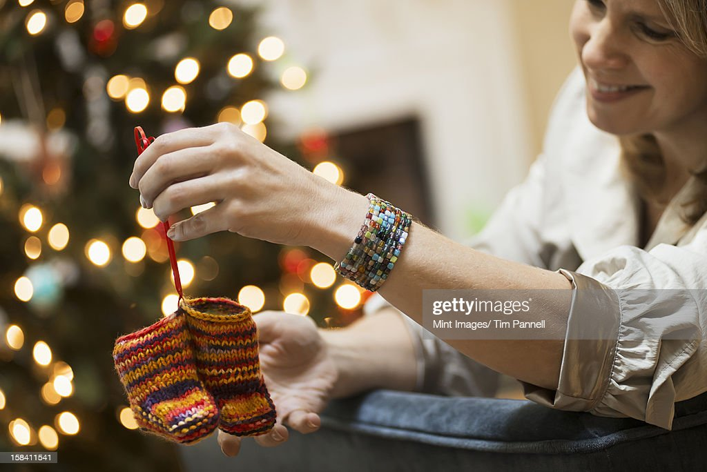 A young woman holding a pair of hand knitted baby booties. : Bildbanksbilder