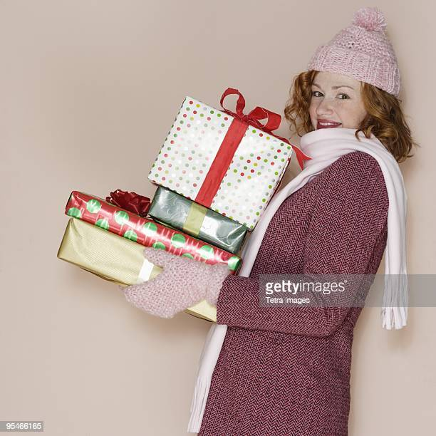 A young woman holding a pile of Christmas presents