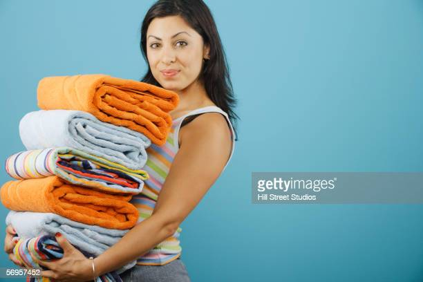 Young woman holding a pile of clean towels