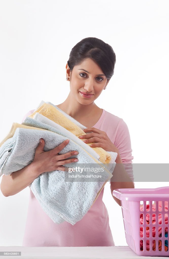 Young woman holding a pile of towels : Stock Photo