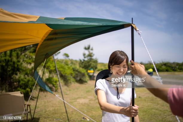 young woman holding a pole to set up tarpaulin - tarpaulin stock pictures, royalty-free photos & images