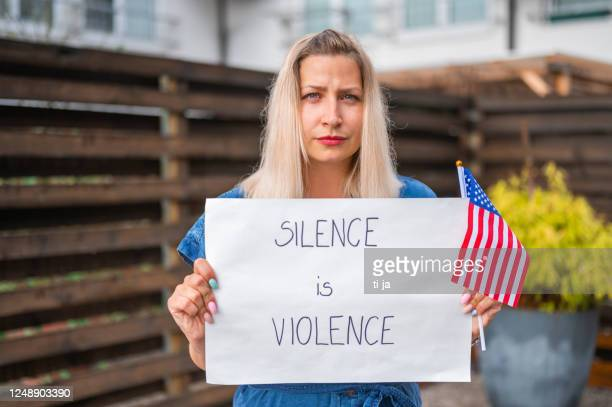 young woman holding a poster with anti-racist message - anti racism stock pictures, royalty-free photos & images