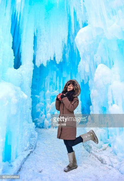 young woman holding a red cup in a parka outside in the cold by ice kicking her leg up smiling - parka coat stock photos and pictures
