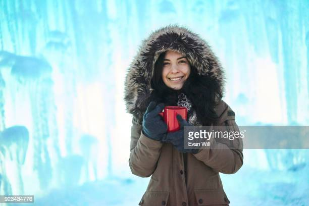 Young woman holding a red cup outside in the cold by ice looking into the camera