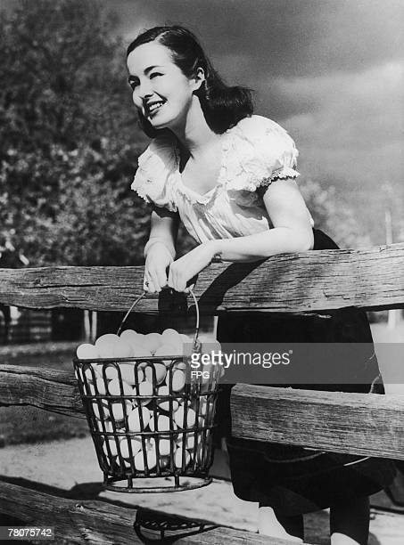A young woman holding a rubbercovered egg basket designed to reduce breakages 1946