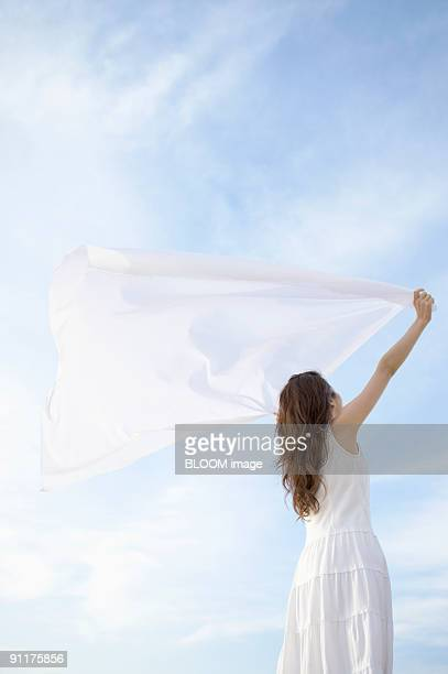 young woman holding a scarf streaming in the wind - ストール ストックフォトと画像