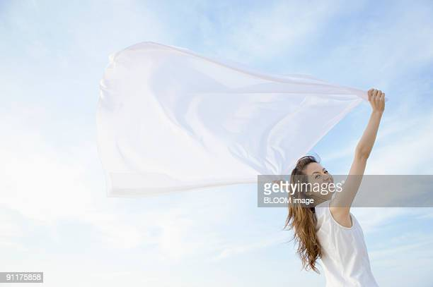 Young woman holding a scarf streaming in the wind