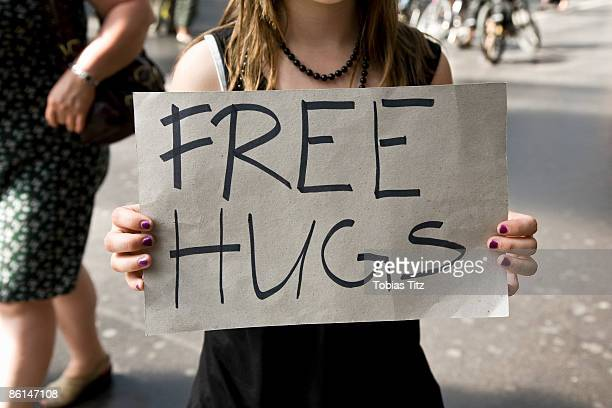 A young woman holding a sign saying Free Hugs