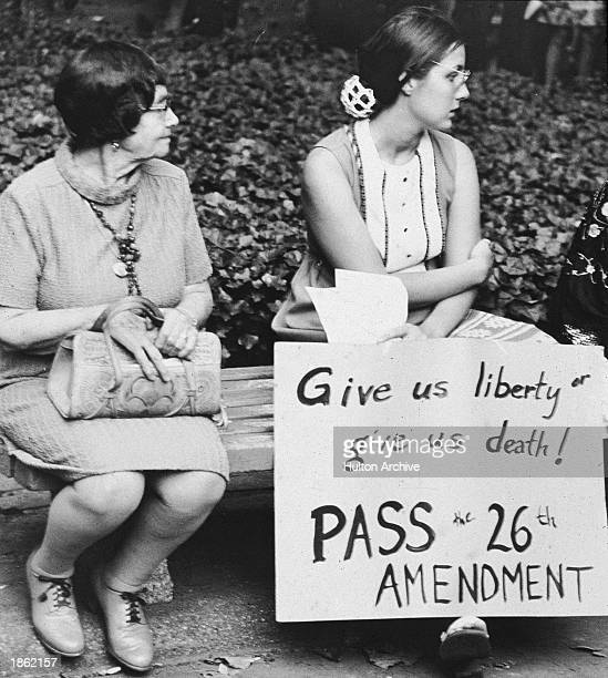 Young woman holding a sign that reads 'Give us liberty or give us death Pass the 26th Amendment' while sitting next to a middleaged woman on a bench...