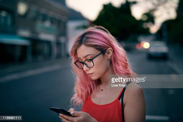 young woman holding a smart phone - pink hair stock pictures, royalty-free photos & images