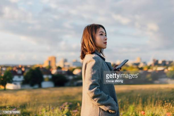 young woman holding a smart phone, watching sunrise at the park - standing stock pictures, royalty-free photos & images