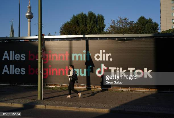 Young woman holding a smartphone walks past an advertisement for social media company TikTok on September 21, 2020 in Berlin, Germany. U.S. President...