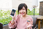 Young woman holding a smartphone with a selfie of her holding a cupcake
