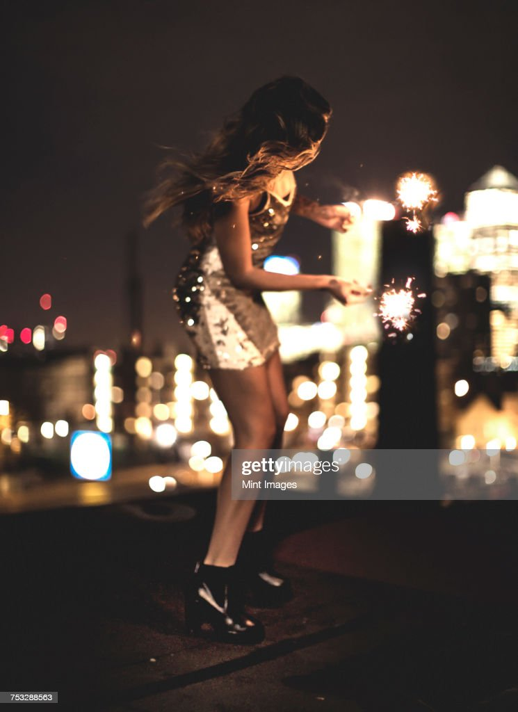 A young woman holding a sparkler and dancing on a building rooftop at night : Stock Photo