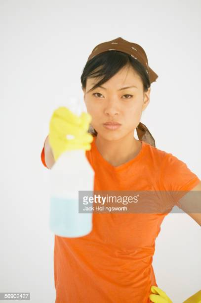 young woman holding a spray bottle - clorox bleach stock pictures, royalty-free photos & images