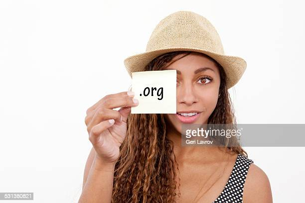 Young woman holding a sticky note labeled '.org'