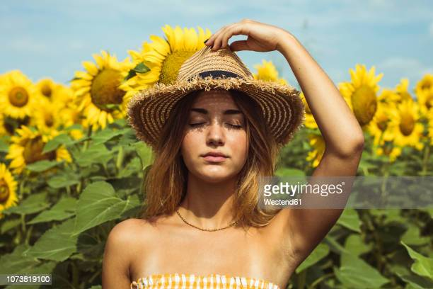 young woman holding a straw hat on her head in a field of sunflowers - yellow hat stock pictures, royalty-free photos & images