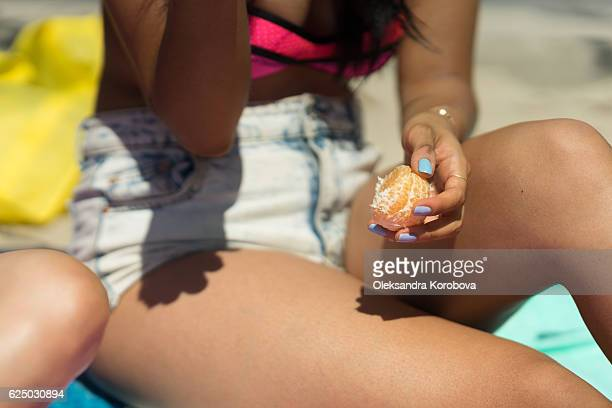 Young woman holding a tangerine on a beach.