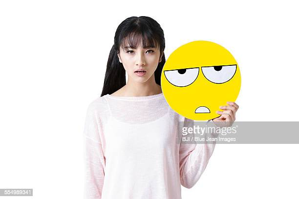 Young woman holding a tired emoticon face