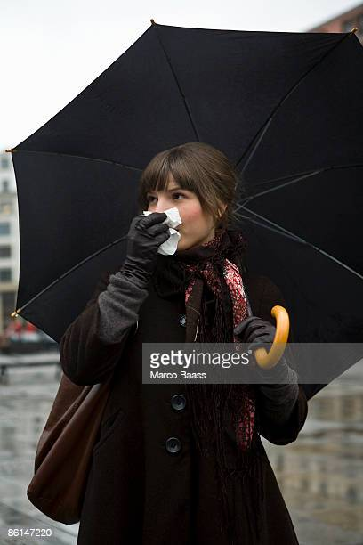 Young woman holding a tissue and an umbrella