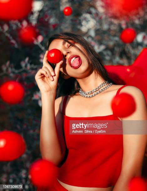 young woman holding a tomato - strapless dress stock pictures, royalty-free photos & images