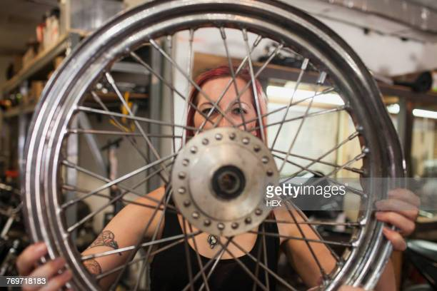 A young woman holding a wheel.