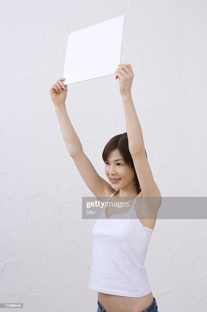 Young woman holding a white board, smiling, side view : Photo