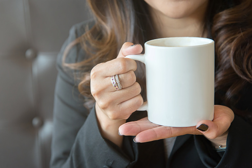 Young woman holding a white coffee cup with two hands outdoors. 1176275746