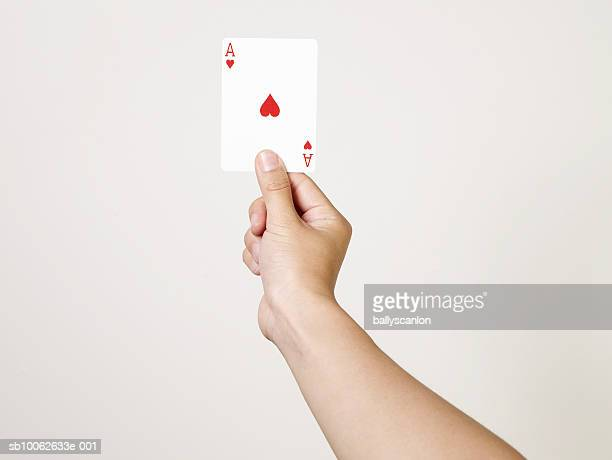 Young woman holding ace of hearts playing card, close-up of arm and hand, studio shot