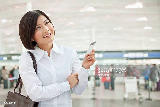 Young Woman Holding an Airplane Ticket