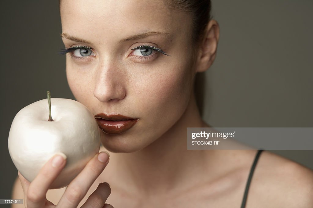 Young woman holding an apple : Photo