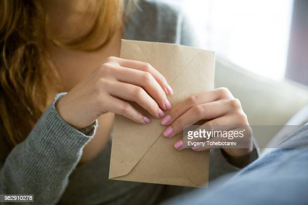 a young woman holding an envelope. - envelope stock pictures, royalty-free photos & images