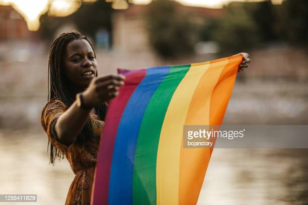 young woman holding an lgbtqi rainbow flag - social movement stock pictures, royalty-free photos & images