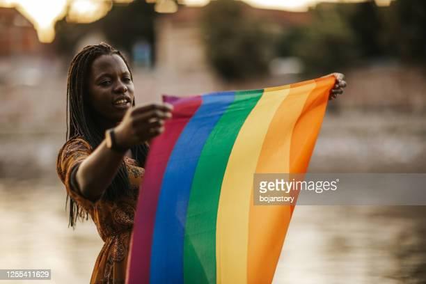 lgbtqi虹の旗を持つ若い女性 - 社会運動 ストックフォトと画像