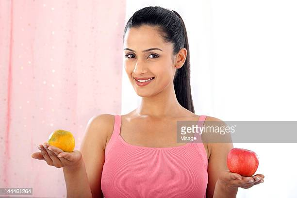Young woman holding an orange and an apple