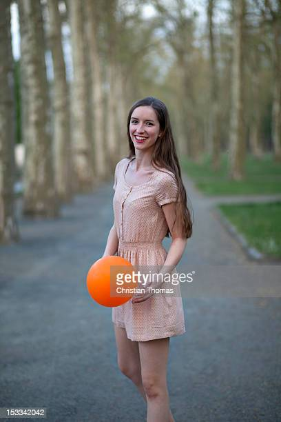 a young woman holding an orange ball, standing in a park - one teenage girl only stock pictures, royalty-free photos & images