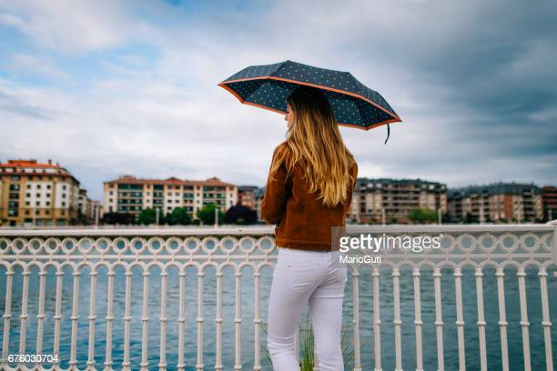 young woman holding an umbrella - mojado stock pictures, royalty-free photos & images