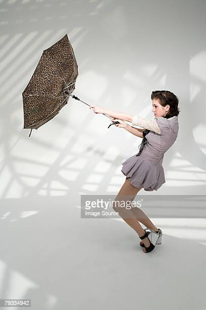 young woman holding an umbrella - inside out stock pictures, royalty-free photos & images
