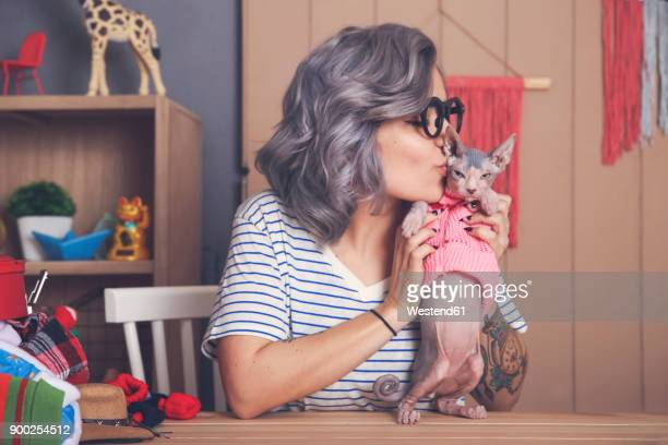 Young woman holding and kissing Sphynx cat wearing pullover