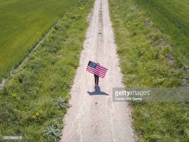Young woman holding and waving an American Flag in a green wheat field