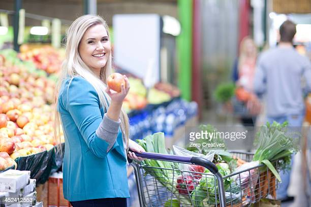 Young woman holding apple in indoor market